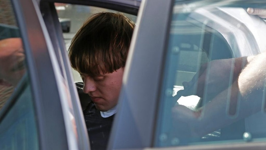 FILE - In this June 18, 2015 file photo,  Dylann Storm Roof sits inside a police car as he is escorted from the Sheby Police Department in Shelby, N.C.  Roof is accused of killing nine people inside Emanuel African Methodist Episcopal Church in Charleston on June 17.  (AP Photo/Chuck Burton)