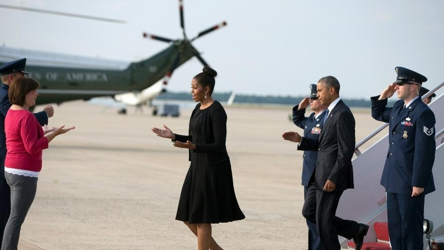 President Barack Obama and first lady Michelle Obama are greeted by Col. John Millard and his wife Jamie as they arrive on Air Force One, Friday, June 26, 2015, in Andrews Air Force Base, Md, as they return from Charleston, S.C., where they attended services honoring the life of Reverend Clementa Pinckney at the College of Charleston TD Arena. Pinckney was one of the nine people killed in the shooting at Emanuel AME Church last week in Charleston. (AP Photo/Carolyn Kaster)