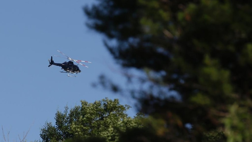 A helicopter flies over the search area for convicted murderer David Sweat, Saturday, June 27, 2015, in Malone, N.Y.  Convicted murderer Richard Matt was shot and killed by a Border Patrol agent in a wooded area about 30 miles from the Clinton Correctional Facility on Friday.  Sweat is on the run, authorities said. (AP Photo/Mary Altaffer)