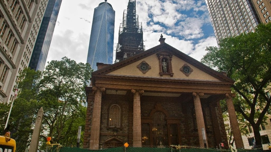 "The  World Trade Center looms behind St. Paul's Chapel with its steeple wrapped in scaffolding for repairs, Thursday, June 25, 2015, in New York.  The winner of a new competition open to people of all faiths called ""The Reconciliation Preaching Prize,"" will have the privilege of delivering an original sermon on Sept. 11 at the chapel near ground zero.  It was turned into a makeshift memorial shrine and became a place of rest and renewal for volunteers and responders, following the terrorist attacks that brought down the twin towers. (AP Photo/Bebeto Matthews)"