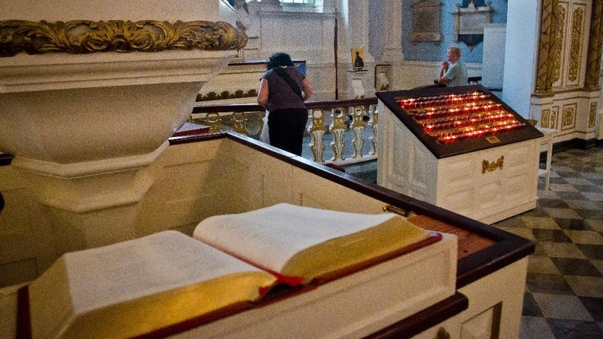 "Visitors pray near the main pew at St. Paul's Chapel, Thursday, June 25, 2015, in New York.  The winner of a new competition open to people of all faiths called ""The Reconciliation Preaching Prize,"" will have the privilege of delivering an original sermon on Sept. 11 at the chapel near ground zero.  It was turned into a makeshift memorial shrine and became a place of rest and renewal for volunteers and responders, following the terrorist attacks that brought down the twin towers. (AP Photo/Bebeto Matthews)"