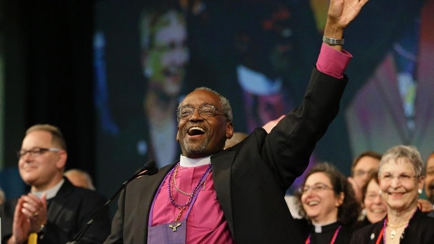 Bishop Michael Curry, of North Carolina, waves to the crowd after being elected the Episcopal Church's first African-American presiding bishop at the Episcopal General Convention Saturday, June 27, 2015, in Salt Lake City. Curry won the vote in a landslide. (AP Photo/Rick Bowmer)