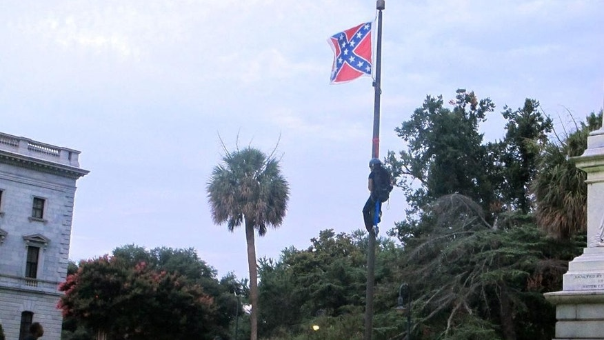 Police surround the flagpole flying the Confederate battle flag at a Confederate monument  at the Statehouse in Columbia, S.C., on Saturday, June, 27, 2015 as Bree Newsome of Charlotte, N.C. climbs the pole to remove the banner. She was taken into custody when she came down. The flag was raised again by capitol workers about 45 minutes later.  (AP Photo/Bruce Smith)
