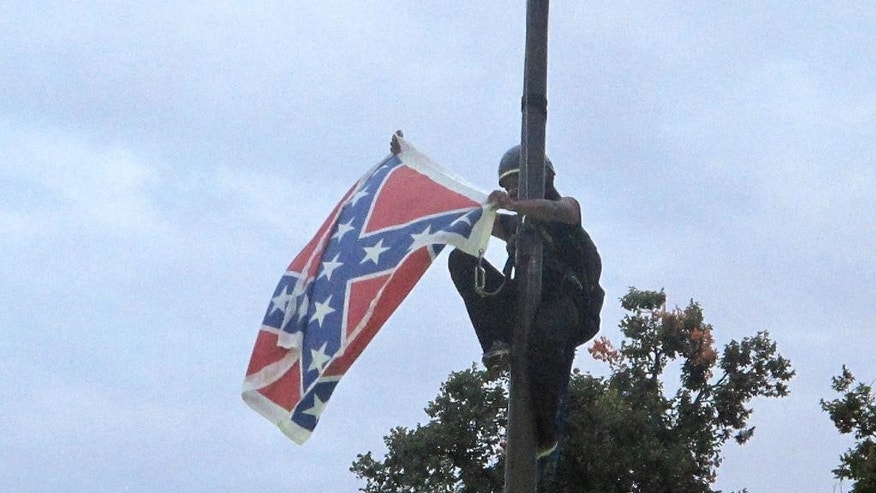 Bree Newsome of Charlotte, N.C., removes the Confederate battle flag at a Confederate monument at the Statehouse in Columbia, S.C., on Saturday, June, 27, 2015. She was taken into custody when she came down. The flag was raised again by capitol workers about 45 minutes later.  (AP Photo/Bruce Smith)