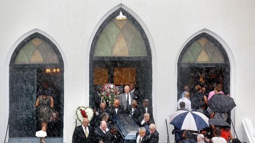 Rain falls as pallbearers exit Emanuel AME Church carrying the casket of Cynthia Hurd as mourners for Susie Jackson and Tywanza Sanders file inside the church for their funerals Saturday, June 27, 2015, in Charleston, S.C. Hurd, Jackson and Sanders were three of the nine people killed in the shooting at the church on June 17. (Grace Beahm/The Post And Courier via AP)