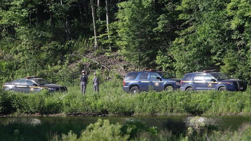 New York State officers stand near the road block at the perimeter of the search area for convicted murderer David Sweat, Saturday, June 27, 2015, in Malone, N.Y.  Convicted murderer Richard Matt was shot and killed by a Border Patrol agent in a wooded area about 30 miles from the Clinton Correctional Facility on Friday.  Sweat is on the run, authorities said. (AP Photo/Mary Altaffer)