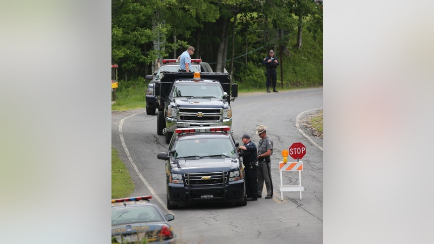 Law enforcement officers work at a roadblock on Saturday, June 27, 2015, in Malone, N.Y. The shooting death of one escaped killer brought new energy to the three-week hunt for a second escaped murderer in the United States as helicopters, search dogs and hundreds of law enforcement officers converged on a wooded area 30 miles from Clinton Correctional Facility. (AP Photo/Mike Groll)