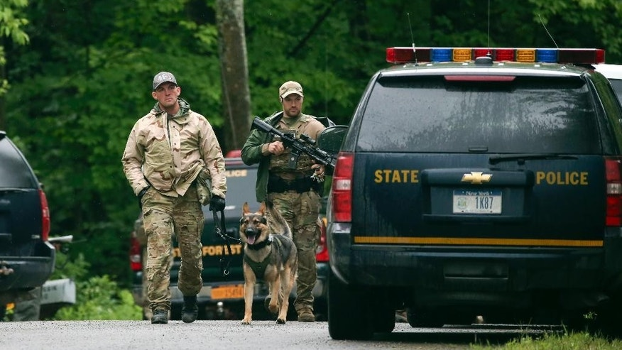 Law enforcement officers walk along a road on Sunday, June 28, 2015, in Malone, N.Y. The shooting death of one escaped killer brought new energy to the three-week hunt for a second escaped murderer in the United States as helicopters, search dogs and hundreds of law enforcement officers converged on a wooded area 30 miles from Clinton Correctional Facility. (AP Photo/Mike Groll)