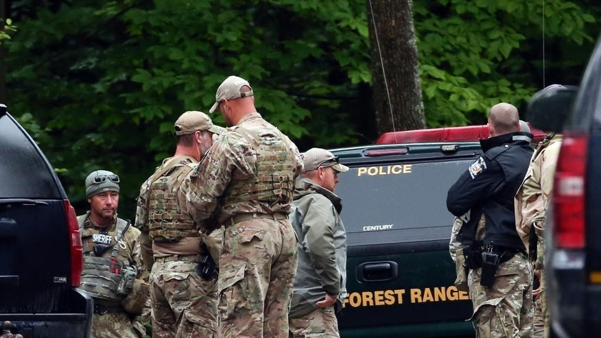 Law enforcement officers gather on a road on Sunday, June 28, 2015, in Malone, N.Y. The shooting death of one escaped killer brought new energy to the three-week hunt for a second escaped murderer in the United States as helicopters, search dogs and hundreds of law enforcement officers converged on a wooded area 30 miles from Clinton Correctional Facility. (AP Photo/Mike Groll)