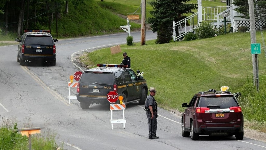 FILE - In this Saturday, June 27, 2015, file photo, New York State Police troopers work a roadblock in Malone, N.Y. Searchers deployed bloodhounds and helicopters, checked houses and car trunks, slogged through swamps and thick underbrush in the Malone area in the search for David Sweat and Richard Matt. Matt was shot and killed Friday, and Sweat was shot and captured Sunday. (AP Photo/Mike Groll, File)