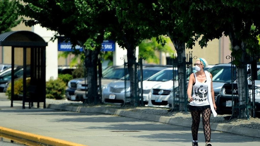 A resident wears a mask while walking in Wenatchee, Wash., near the Blue Bird fruit plant Monday, June 29, 2015. Emergency management officials say ammonia that started leaking from the fruit warehouse burning in a central Washington wildfire has dissipated and is no longer a threat. (Tyler Tjomsland/The Spokesman-Review, via AP)
