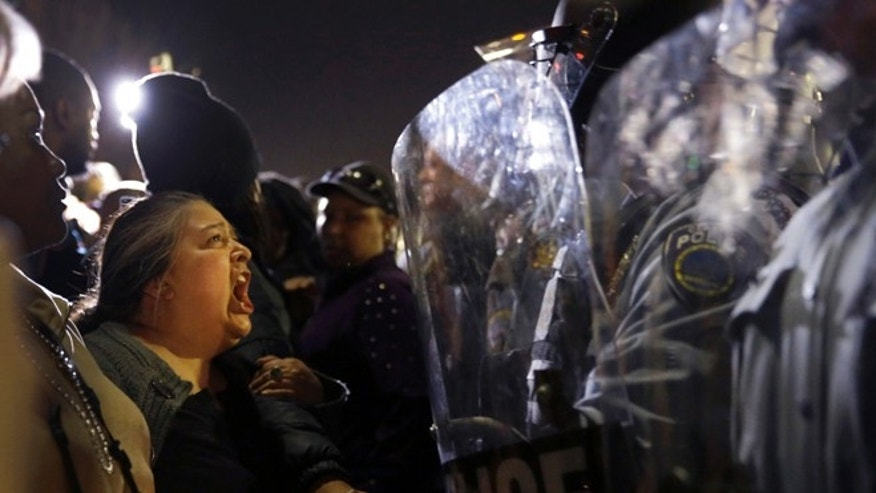 Aug. 11, 2014: In this file photo, a protester yells at police outside the Ferguson, Mo., Police Department. Police antagonized crowds gathered to protest the shooting of 18-year-old Michael Brown in Ferguson, violated free-speech rights and made it difficult to hold officers accountable, according to a U.S. Department of Justice report summary published Tuesday by the St. Louis Post-Dispatch.