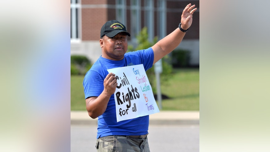 Joe Odicta waves at cars honking in support of the protest of Rowan County Clerk Kim Davis at the Rowan County Judicial Center, Tuesday, June 30, 2015, in Morehead, Ky. Due to the ruling of the Supreme Court of the United States, and her own religious beliefs, Davis has refused to issue any marriage licenses in the county. (AP Photo/Timothy D. Easley)