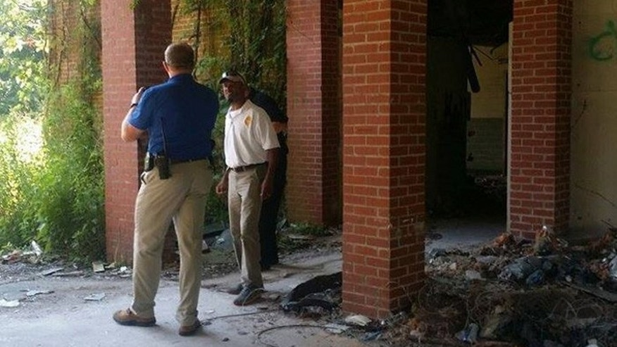 Investigators stand outside Kuhn Memorial State Hospital, in Vicksburg, Miss., where ghost hunters found the body of an apparent murder victim. (Photo by David Childers, via The Clarion-Ledger)