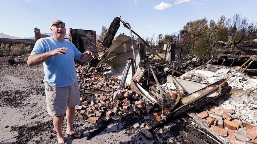 Tom Bryant describes the fire that destroyed his home the night before, Monday, June 29, 2015, in Wenatchee, Wash. The wildfire fueled by high temperatures and strong winds roared into town Sunday afternoon. The blaze ignited in brush just outside Wenatchee, quickly burning out of control. (AP Photo/Elaine Thompson)