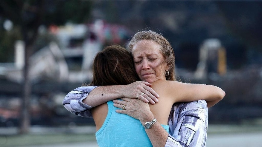 Julie Smith, right, embraces her neighbor Renee Monson as they stand near the remains of Smith's home, destroyed in a wildfire the night before, Monday, June 29, 2015, in Wenatchee, Wash. The wildfire fueled by high temperatures and strong winds roared into town Sunday afternoon. The blaze ignited in brush just outside Wenatchee, quickly burning out of control. (AP Photo/Elaine Thompson)