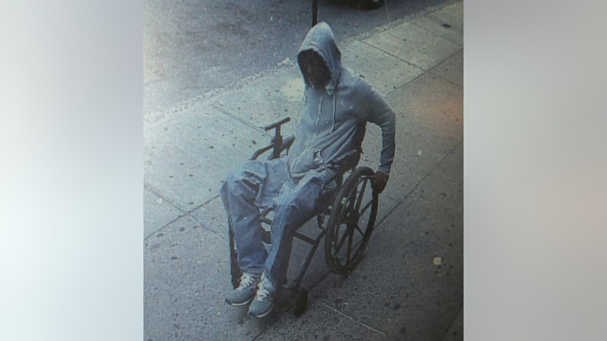 In this Monday, June 29, 2015 photo provided by the New York Police Department, a man gets away after he robbed the Santander bank in the Queens borough of New York. After receiving over $1,200 in bills, police say the suspect then fled westbound on Broadway in the wheelchair. He remains at large. (NYPD via AP)