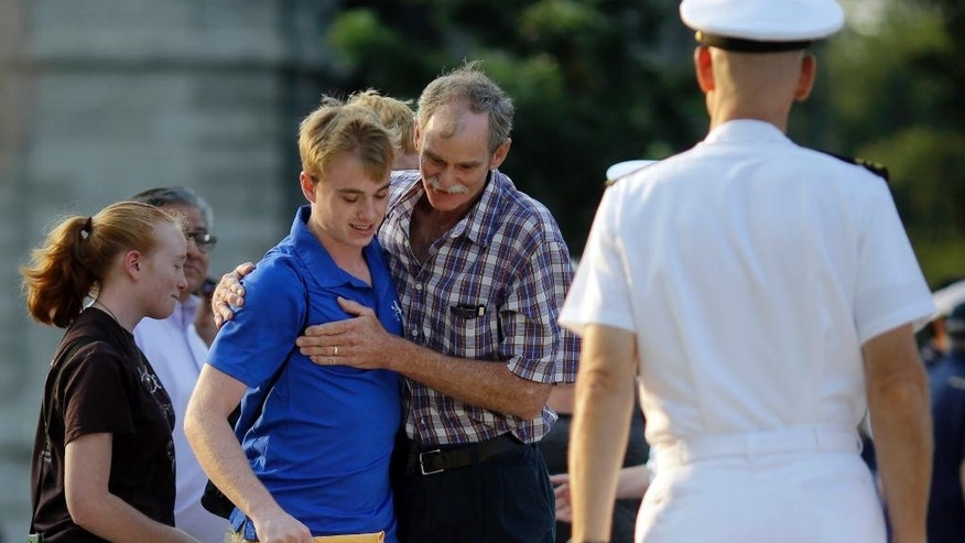 "Jim Johnston, center, of Chapel Hill, N.C., embraces his son, prospective plebe Dan Johnston, before watching him enter Induction Day at the U.S. Naval Academy, Wednesday, July 1, 2015, in Annapolis, Md. More than 1,100 young men and women reported for ""I-Day,"" where they received haircuts, medical examinations, new uniforms and instructions on how to salute and address superiors before taking an oath of office to become members of academy's newest class. (AP Photo/Patrick Semansky)"