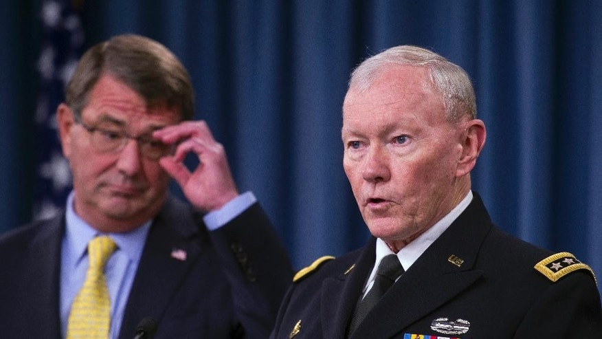 Defense Secretary Ash Carter listens at left as Joint Chefs Chairman Gen, Martin Dempsey speaks during a briefing at the Pentagon, Wednesday, July 1, 2015. (AP Photo/Cliff Owen)