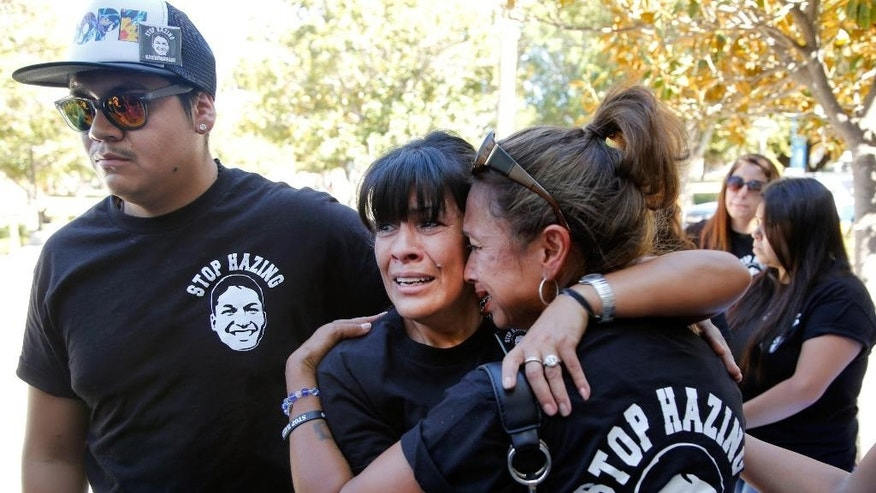 FILE - In this Sept. 5, 2014, file photo, relatives of the late Armando Villa, Joshua Castaneda, left, and his mother Martha Castaneda and Villa's aunt, Maria Castaneda, right, react, as California State University, Northridge CSUN President Dianne Harrison, reads a statement regarding Pi Kappa Phi Fraternity activities that lead to the death of CSUN student Armando Villa, at a news conference at the CSUN campus in Northridge, Calif. The family of the California college student who died during a fraternity hike sued the organization and the school on Wednesday, July 1, 2015, saying the young man's death was senseless and easily preventable. (AP Photo/Damian Dovarganes, File)