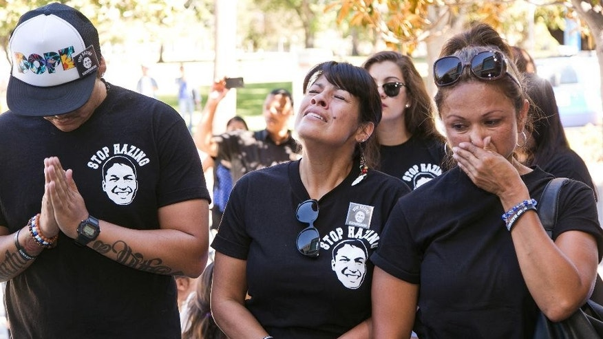 FILE - In this Sept. 5, 2014, file photo, relatives of the late Armando Villa, Joshua Castaneda, left, and his mother Martha Castaneda, and Villa's aunt, Maria Castaneda, right, react as California State University, Northridge CSUN President Dianne Harrison, reads a statement regarding Pi Kappa Phi Fraternity activities that lead to the death of CSUN student Armando Villa, at a news conference at the CSUN campus in Northridge, Calif. The family of the California college student who died during a fraternity hike sued the organization and the school on Wednesday, July 1, 2015, saying the young man's death was senseless and easily preventable. (AP Photo/Damian Dovarganes, File)