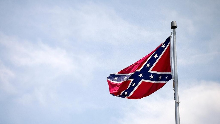 "A Confederate flag flies at the base of Stone Mountain Tuesday, June 30, 2015, in Stone Mountain, Ga. At Georgia's iconic Stone Mountain, where the Confederacy is enshrined in a giant bas-relief sculpture, the Ku Klux Klan once held notorious cross-burnings and rebel battle flags still wave prominently, officials are considering what to do about those flags. The park, which now offers family-friendly fireworks and laser light shows, is readying its ""Fantastic Fourth Celebration"" Thursday through Sunday, and multiple Confederate flag varieties are still displayed at the mountain's base. (AP Photo/David Goldman)"