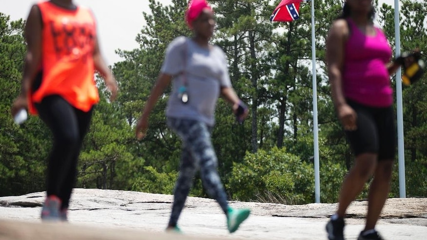 "Visitors pass a Confederate flag as it flies at the base of Stone Mountain Tuesday, June 30, 2015, in Stone Mountain, Ga. At Georgia's iconic Stone Mountain — where the Confederacy is enshrined in a giant bas-relief sculpture, the Ku Klux Klan once held notorious cross-burnings and large Confederate flags still wave prominently — officials are considering what to do about those flags. The park, which now offers family-friendly fireworks and laser light shows, is readying its ""Fantastic Fourth Celebration"" Thursday through Sunday, and multiple Confederate flag varieties are still displayed at the mountain's base. (AP Photo/David Goldman)"