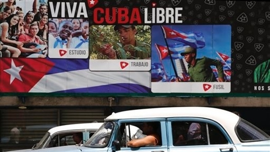"A classic American car passes in front of some signs that reads in Spanish ""Long Live Free Cuba"" in Havana, Cuba, Tuesday, June 16, 2015. Six months ago Wednesday, Presidents Barack Obama and Raul Castro stunned the world by announcing an end to their nations half-century of official hostility. In Cuba, aging leaders fear swift, uncontrolled change that would cost them power and spawn disorder in a country that dreads the violence and inequality scarring its neighbors. That fear is heightened by the United States long history of trying to topple Castro and his brother Fidel. (AP Photo/Desmond Boylan)"