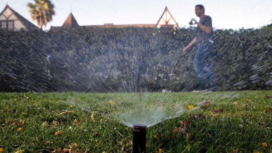 FILE - In this June 5, 2015, file photo, Tony Corcoran records sprinklers watering the lawn in front of a house in Beverly Hills, Calif. California's drought-stricken cities set a record for water conservation, reducing usage 29 percent in May, according to data released by a state agency Wednesday, July 1, 2015. (AP Photo/Jae C. Hong, File)