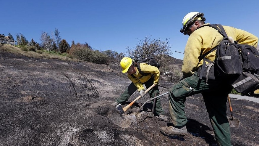 Firefighters Kelly Willman, left, and Jessie Salazar work to put out still smoldering hot spots from a wildfire two days earlier, Tuesday, June 30, 2015, in Wenatchee, Wash. Two dozen homes were destroyed in a fast-moving wildfire Sunday night in this central Washington city about 120 miles east of Seattle. A handful of businesses also were destroyed when flames spread to the downtown core. (AP Photo/Elaine Thompson)