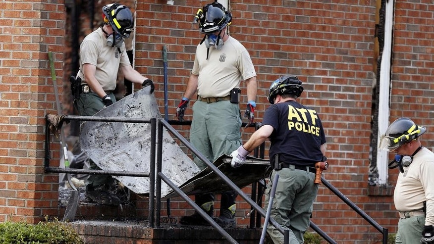 Investigators from the Bureau of Alcohol, Tobacco, Firearms and Explosives and the South Carolina Law Enforcement Division remove the remains of a door from the Mount Zion African Methodist Episcopal Church, Wednesday, July 1, 2015, in Greeleyville, S.C. The African-American church, which was burned down by the Ku Klux Klan in 1995, caught fire Tuesday night, but authorities said arson is not the cause. (Veasey Conway/The Morning News via AP)