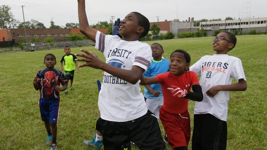 In this photo taken June 17, 2015, kids play football in McKenzie Field in Highland Park, Mich. Former NFL star and Highland Park native Reggie McKenzie had to go into his own pocket to have the city-owned field mowed in time for an annual youth football camp. The field in the Detroit enclave was overgrown with nearly waist-high weeds and grass about a week before the 3-day camp started in June. (AP Photo/Carlos Osorio)