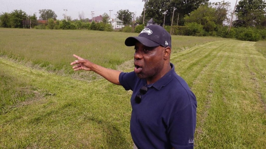 In this photo taken May 29, 2015, former NFL star and Highland Park native Reggie McKenzie stands in the field named in his honor in Highland Park, Mich. McKenzie had to go into his own pocket to have the city-owned field mowed in time for an annual youth football camp. The field in the Detroit enclave was overgrown with nearly waist-high weeds and grass about a week before the 3-day camp started in June. (AP Photo/Carlos Osorio)