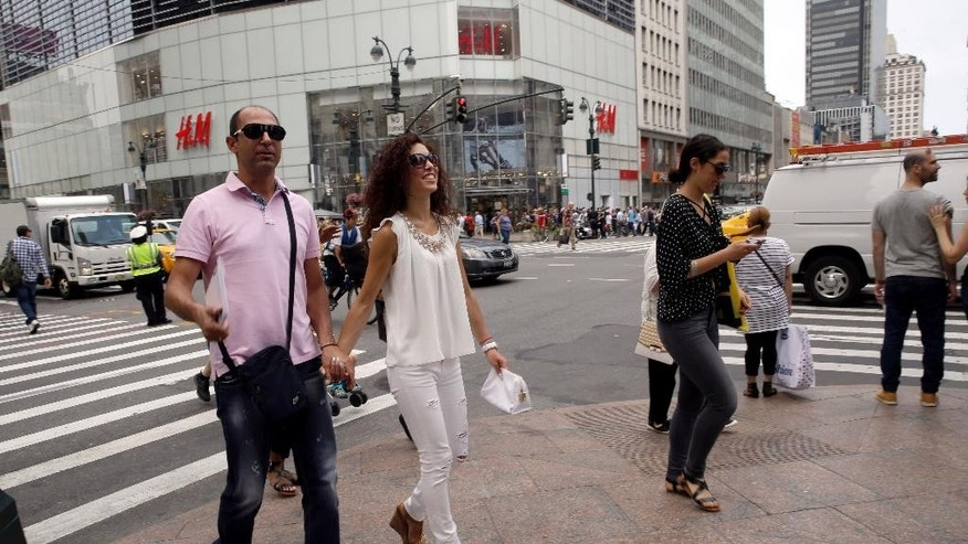 "Newlyweds Valasia Limnioti, right, and Konstantinos Patronis walk along 34th Street and 6th Avenue in Midtown Manhattan, Thursday, July 2, 2015, in New York. The couple topped ""the dream trip of our lives"" in New York City, where their three-week honeymoon turned into a nightmare: Their Greek-issued credit cards were suddenly declined and they were left nearly penniless. Strangers from two Greek Orthodox churches in Queens came to their rescue, giving them survival cash until their flight home to Greece this Friday. (AP Photo/Mary Altaffer)"
