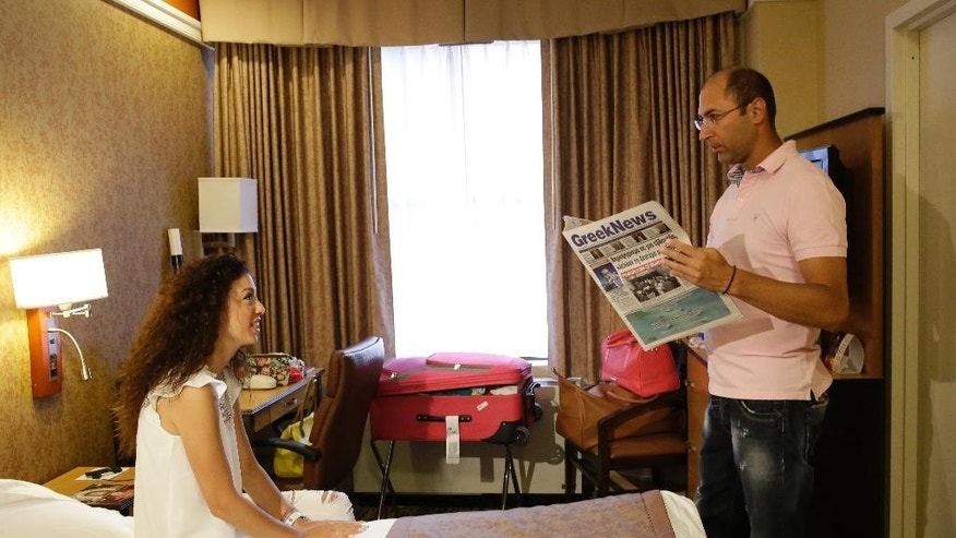 "Newlyweds Valasia Limnioti, left, and Konstantinos Patronis talk to one another in their hotel room in Midtown Manhattan, Thursday, July 2, 2015, in New York. The couple topped ""the dream trip of our lives"" in New York City, where their three-week honeymoon turned into a nightmare: Their Greek-issued credit cards were suddenly declined and they were left nearly penniless. Strangers from two Greek Orthodox churches in Queens came to their rescue, giving them survival cash until their flight home to Greece this Friday. (AP Photo/Mary Altaffer)"