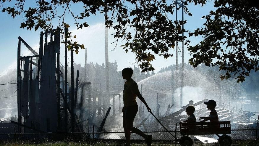 Beth Wirth, left, pulls her sons Emmett Wirth, 2, and Anderson Wirth, 5, in a wagon during a visit to the still smoldering Civic Stadium, Tuesday, June 30, 2015, in Eugene, Ore. A fire destroyed Eugene's historic Civic Stadium on Monday evening and prompted the temporary evacuation of a two-block area, the fire chief said. (Chris Pietsch/The Register-Guard via AP)