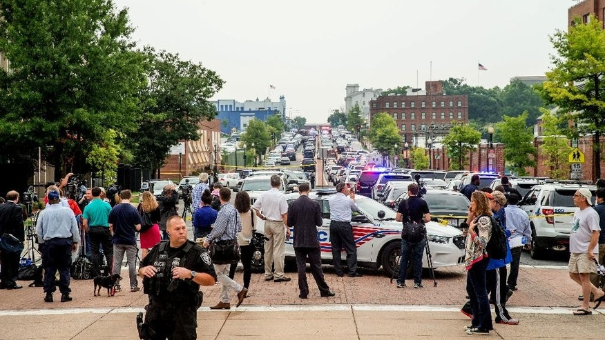 Members of the media and pedestrians gather along M St. in Southeast Washington, Thursday, July 2, 2015. The Washington Navy Yard was on lockdown Thursday morning after reports of gunshots, but a senior federal law enforcement official says there has been no confirmed report of any shooting.  (AP Photo/Andrew Harnik)