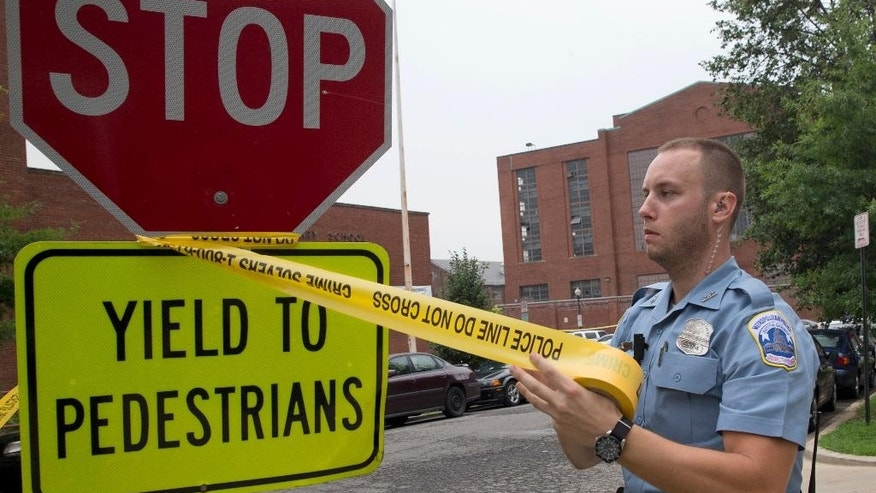 A police officer puts up police tape near the Navy Yard in Washington, Thursday, July 2, 2015. The Washington Navy Yard was on lockdown Thursday morning after reports of gunshots, but a senior federal law enforcement official says there has been no confirmed report of any shooting.  (AP Photo/Jacquelyn Martin)