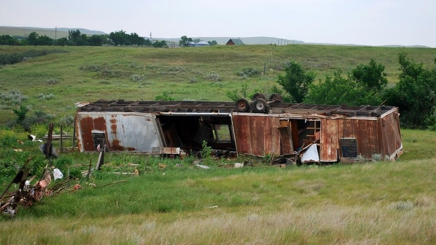 In this Wednesday, July 1, 2015 photo provided by the National Weather Service, a storage trailer is shown after it was flipped during a storm on Tuesday, June 30, 2015 in Sidney, Mont. A supercell thunderstorm that moved through eastern Montana spawned the tornado responsible for the damage. (National Weather Service via AP)