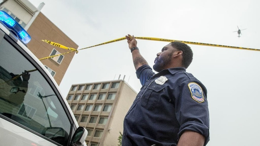 A helicopter hovers above a police officer holding up police tape for a vehicle as a large police presence gathers along M St. Southeast in Washington, Thursday, July 2, 2015, near the Washington Navy Yard campus. The Washington Navy Yard was on lockdown Thursday morning after reports of gunshots, but a senior federal law enforcement official says there has been no confirmed report of any shooting.   (AP Photo/Andrew Harnik)