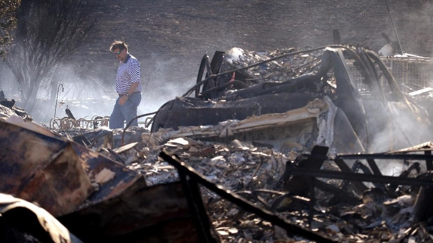 FILE - In this June 29, 2015, file photo, Vern Smith walks through the rubble of his still smoldering home, one of some two dozen destroyed in a wildfire the night before, in Wenatchee, Wash. Predictions of an early wildfire season have come true in Washington as crews battle small and large blazes across the state. (AP Photo/Elaine Thompson, File)