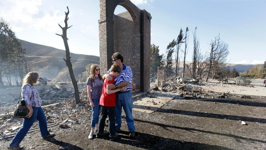 FILE - In this June 29, 2015, file photo, Vern Smith, right, embraces his son Spencer, 13, as daughter Mary, 17, stands with them and his wife, Julie, joins them in front of the remains of their fire-destroyed home, one of some two dozen lost in a wildfire the night before, in Wenatchee, Wash. Predictions of an early wildfire season have come true in Washington as crews battle small and large blazes across the state. (AP Photo/Elaine Thompson, File)