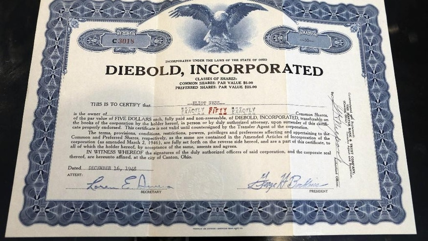 "This photo taken Friday, June 12, 2015, shows a Diebold stock certificate in the name of Elliot Ness, in Fort Lauderdale, Fla. Eliot Ness, the famed Prohibition agent who led the ""Untouchables"" in their crusade against Chicago gangster Al Capone's liquor bootlegging rackets, later became the top executive at bank services company Diebold Inc. Part of his compensation appears to have been company stock that recently surfaced in Florida, sparking a new legal fight between the company and the Ness estate. (AP Photo/Alan Diaz)"