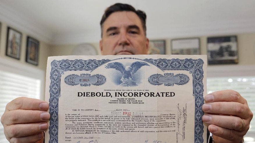 "In this photo taken Friday June 12, 2015, attorney John F. Bradley shows a Diebold stock certificate in the name of Elliot Ness, in Fort Lauderdale, Fla. Ness, the famed Prohibition agent who led the ""Untouchables"" in their crusade against Chicago gangster Al Capone's liquor bootlegging rackets, later became the top executive at bank services company Diebold Inc. Part of his compensation appears to have been company stock that recently surfaced in Florida, sparking a new legal fight between the company and the Ness estate. (AP Photo/Alan Diaz)"