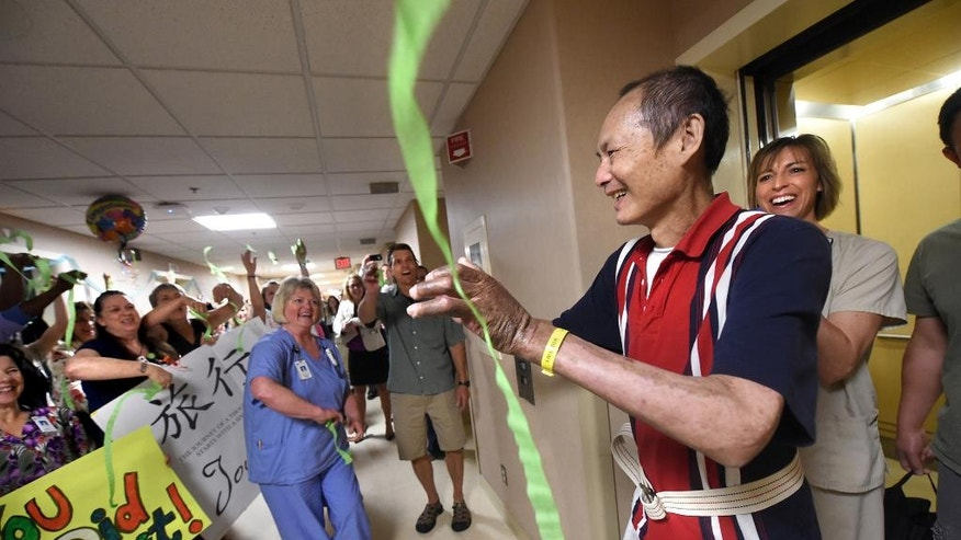 She Yan Chen gets a surprise greeting at Regions Hospital in St. Paul, Minn., when he gets out of an elevator after physical therapy on Thursday, July 2, 2015. Chen, who survived being badly burned in a lawnmower explosion was discharged Friday, July 3 after 264 days in Regions Hospital, but not before his caregivers gathered to say farewell to one of their favorite patients. (Jean Pieri/The St. Paul Pioneer Press via AP)