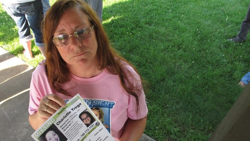 In this June 24, 2015, photo, Yvonne Boggs holds a flier seeking information on her daughter, Charlotte Trego, who has been missing for more than a year, in Chillicothe, Ohio. The fate of six women, four of them dead, two missing for months, have people on edge in the small southern Ohio city of Chillicothe as relatives seek clues, seemingly in vain, to whatever hapened to their loved ones.  (AP Photo/Andrew Welsh-Huggins)