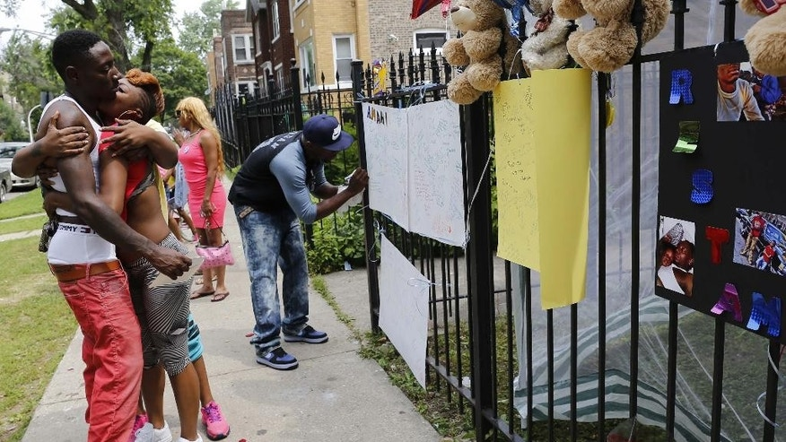 Antonio Brown, left, father of Amari Brown, is embraced by a community member, Monday, July 6, 2015, in Chicago. Authorities say 7-year-old Amari Brown, who was celebrating the Fourth of July with his family, was among three people who were shot and killed overnight during a weekend outbreak of gun-related violence in Chicago. (AP Photo/Christian K. Lee)