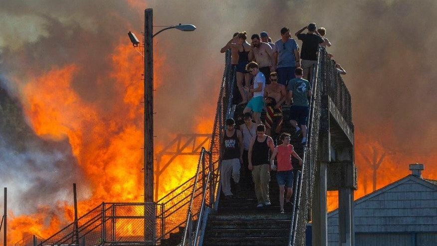 FILE - In this June 29, 2015, file photo, onlookers watch the Civic Stadium burn in Eugene, Ore. Eugene investigators said Thursday, July 2, four boys were playing with fire in the press box of the town's historic stadium, but the flames got out of control and burned down the ballpark. (Andy Nelson/The Register-Guard via AP, File)