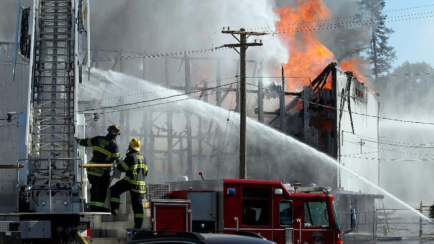 FILE - In this June 29, 2015, file photo, firefighters work to put out a fire at the Civic Stadium in Eugene, Ore. Eugene investigators said Thursday, July 2, four boys were playing with fire in the press box of the town's historic stadium, but the flames got out of control and burned down the ballpark. (Paul Carter/The Register-Guard via AP, File)