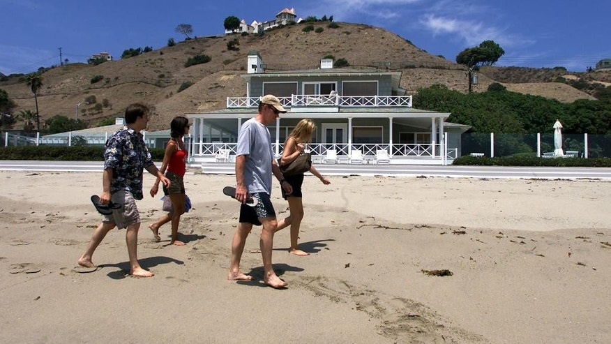 """FILE - In this July 27, 2002 file photo, beachgoers walk past Hollywood mogul David Geffen's home on Carbon Beach in Malibu, Calif. A public accessway to the beach was established next to Geffen's home in 2005. It may be called """"Billionaires' Beach,"""" but the pristine views along one of Malibu's most exclusive coastlines are now more accessible. After a decade-long legal fight that pitted public access advocates against a wealthy homeowner who refused to build a path, the California Coastal Commission will open a third accessway a few hundred yards down the beach from Geffen's home Tuesday, July 7, 2015.(AP Photo/Damian Dovarganes, File)"""